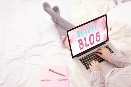 using laptop: Woman using laptop on her bed. Blog concept