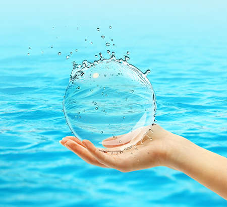 Female hand holding water ball splash on blue water background