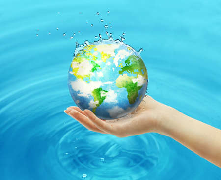 Female hand holding globe on blue water background