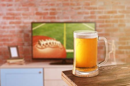television show: Glass of beer on wooden table in front of television show of football. Watching football match at home.