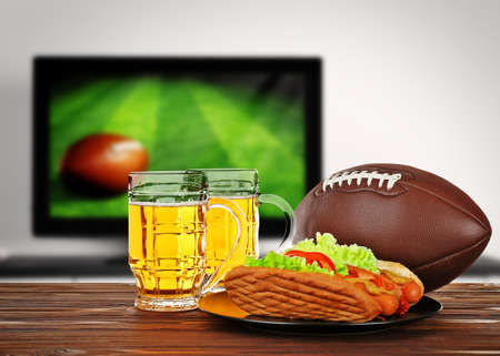 television show: Two glasses of beer, ball and snack on wooden table in front of television show of football. Watching football match at home.