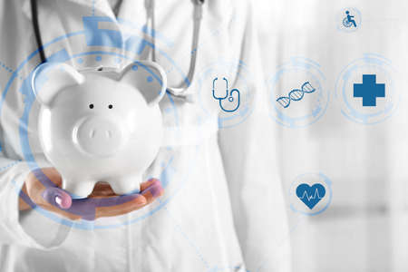 doctor money: Doctor hands with piggy bank. Medical technology concept Stock Photo