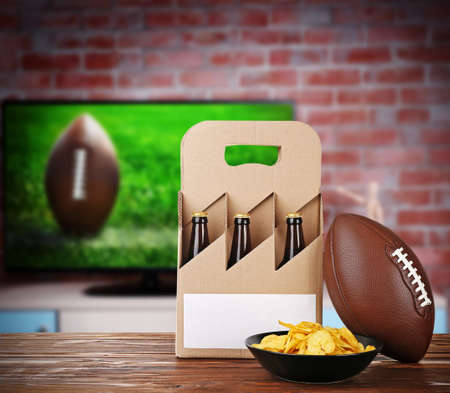 television show: Six pack of beer, snack and ball on wooden table in front of television show of football. Watching football match at home.