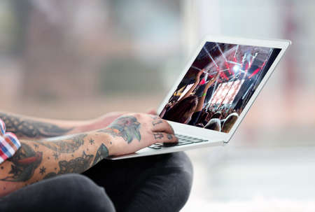 computer club: Young man with tattoo using laptop on a floor at home