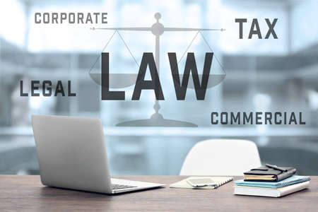 Law concept. Lawyer workplace with laptop and text design on blurred background.