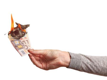 Female hand holding burning euro banknotes on white background.