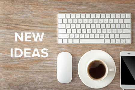 Business training concept. Keyboard, phone and cup of coffee on a wooden desk background, top view Фото со стока