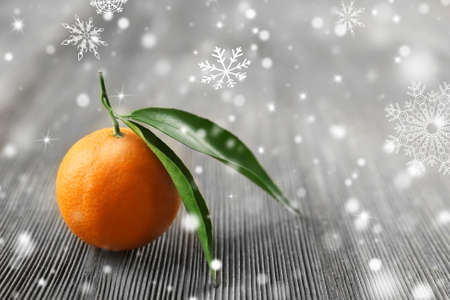Fresh tangerines with leaves on wooden table, closeup. Snow effect