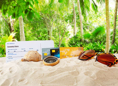 Credit cards, boarding pass and sunglasses on beach.