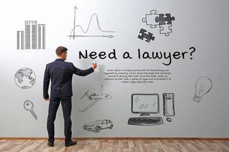 Man writing NEED A LAWYER on grey wall