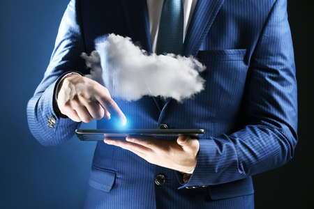 Businessman using tablet on blue background. Cloud computing and information storage concept. Stock Photo