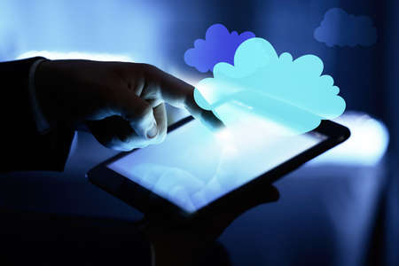 Businessman using tablet on blurred background. Cloud computing and information storage concept.
