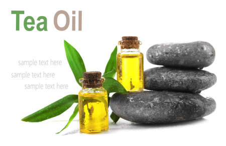 Bottles with tea tree essence and spa stones on white background. Space for text. Stock Photo - 77478923