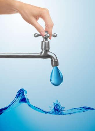 Conservation water-concept. Vrouwelijke hand draaiende kraan uit. Stockfoto