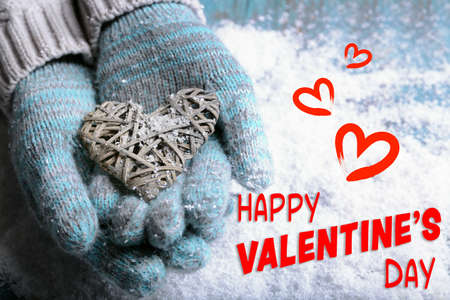 Female hands in mittens holding heart on snow background. Text happy valentines day.