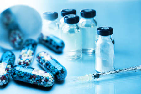Heap of pills and vaccine in vial with syringe on light blue background Stock Photo - 77458696