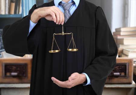Rechter die schalen van rechtvaardigheid op vage boekenachtergrond houden. Stockfoto - 77305369