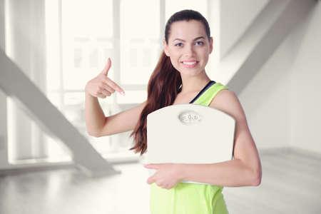 levantar peso: Mujer hermosa joven con la botella y las escalas en fondo borroso del pasillo.