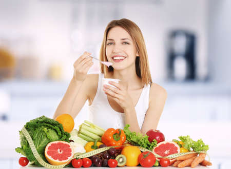 Beautiful young woman with yogurt and healthy food on blurred kitchen interior background. Diet concept. Stock Photo