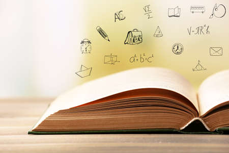 Book on wooden table. Icons on blurred background.