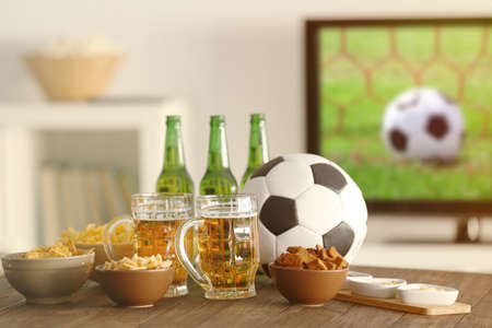 Tasty snacks, beer and ball on kitchen table against blurred background