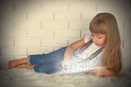 Little girl with tablet on brick wall background. Study and technology concept. Stock Photo