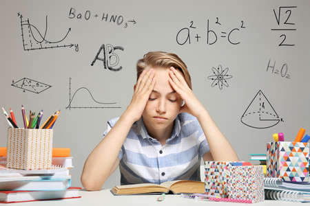 Tired boy studying at table. Different subjects signs on gray background. Education concept. Stock Photo