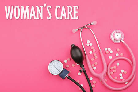 Gynecology concept. Stethoscope with pills on color background