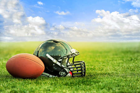 Rugby helmet with ball on green grass and blue sky background Фото со стока