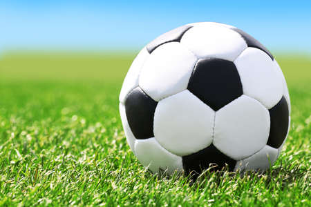 Soccer ball on green grass and blue sky background Stock Photo