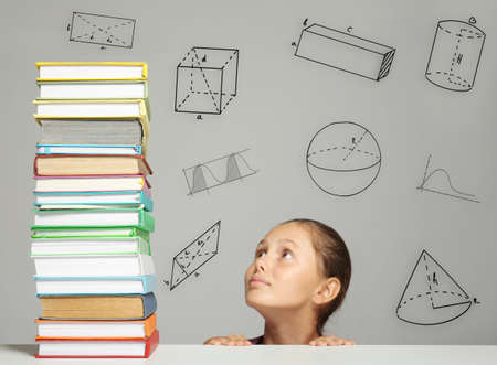 Tired girl looking at big stack of books on table. Geometrical figures on gray background. Education concept. Stock Photo