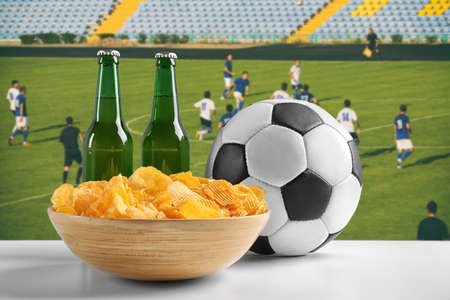 Beer with snacks and football ball on green field background