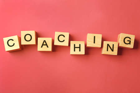 to contemplate: Coaching concept. Wooden cubes on pink background Stock Photo