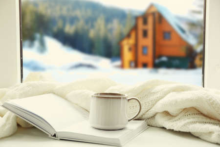 Cup of hot drink and book on the windowsill in winter landscape background Standard-Bild