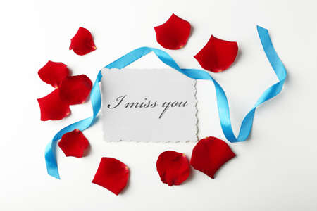 Rose petals, ribbon and card on white background