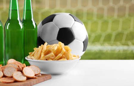 Bal, snacks en flessen bier op tafel tegen voetbal achtergrond