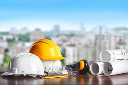 Concepto de construcción. Equipo de arquitecto: cascos, plano y lápiz sobre la mesa y vista de la ciudad Foto de archivo - 83246590