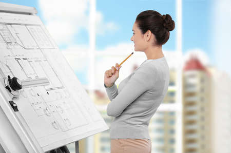 Young female engineer working with project on drawing board in office Stockfoto