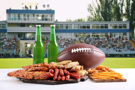 Rugby ball, snacks and bottles of beer on football field background Stock Photo