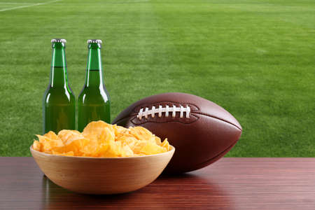 Rugby ball, chips and bottles of beer on green field background Stock Photo