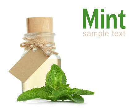 Glass bottle of essential oil, closeup. Word MINT on white background. Spa beauty concept. Stock Photo