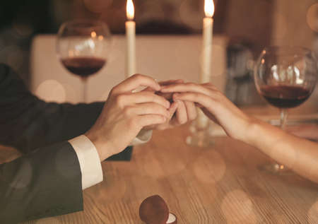 fingers put together: Man making marriage proposal to girlfriend at restaurant, closeup