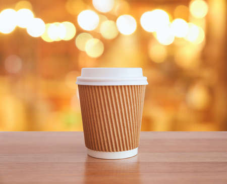 Paper cup of coffee on wooden table against blurred background. Stock Photo