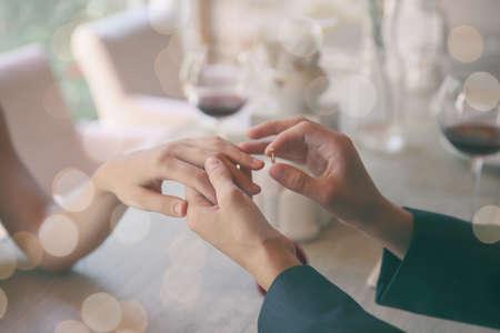Mann macht Heiratsantrag an Freundin im Restaurant, Nahaufnahme Standard-Bild - 85866402