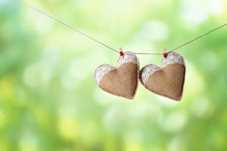Two hearts hanging on rope against blurred green background. Stock Photo