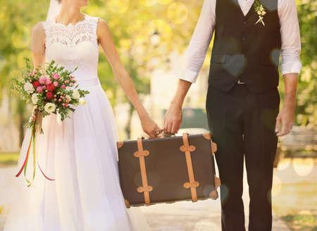 Bruidegom en bruid die uitstekende koffer openlucht houden