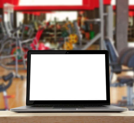Laptop with blank screen on blurred gym background