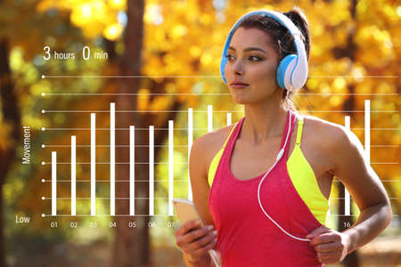 Young woman jogging at park. Graphic of training results. Health care and sport concept. 스톡 콘텐츠