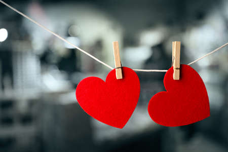 Two red hearts hanging on rope against blurred background. Stock Photo