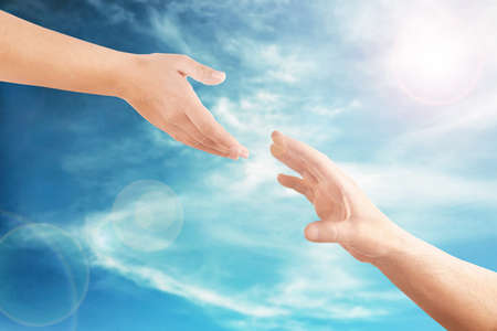 Female and male hands reaching to each other on sky background. Help and care concept.